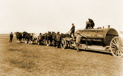 2. Image showing a team of horses pulling a boiler across the prairies
