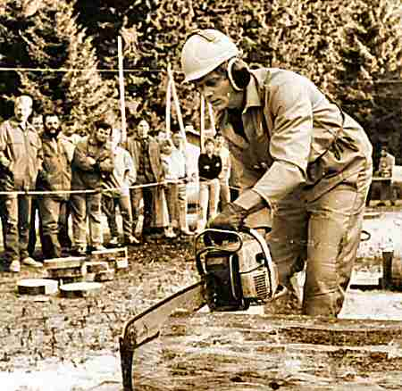 3. Photo of a competitor racing to chop a log with a chainsaw